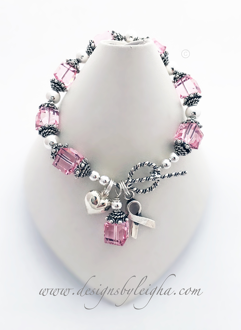 "This ribbon bracelet is shown with pink Swarovski Crystals for Breast Cancer Awareness. The corrdinating pink crystal dangle charm and ribbon charm are included in the price. They picked the Twisted Toggle clasp (free). This bracelet is 6 1/2"" and they added a Puffed Heart Charm."