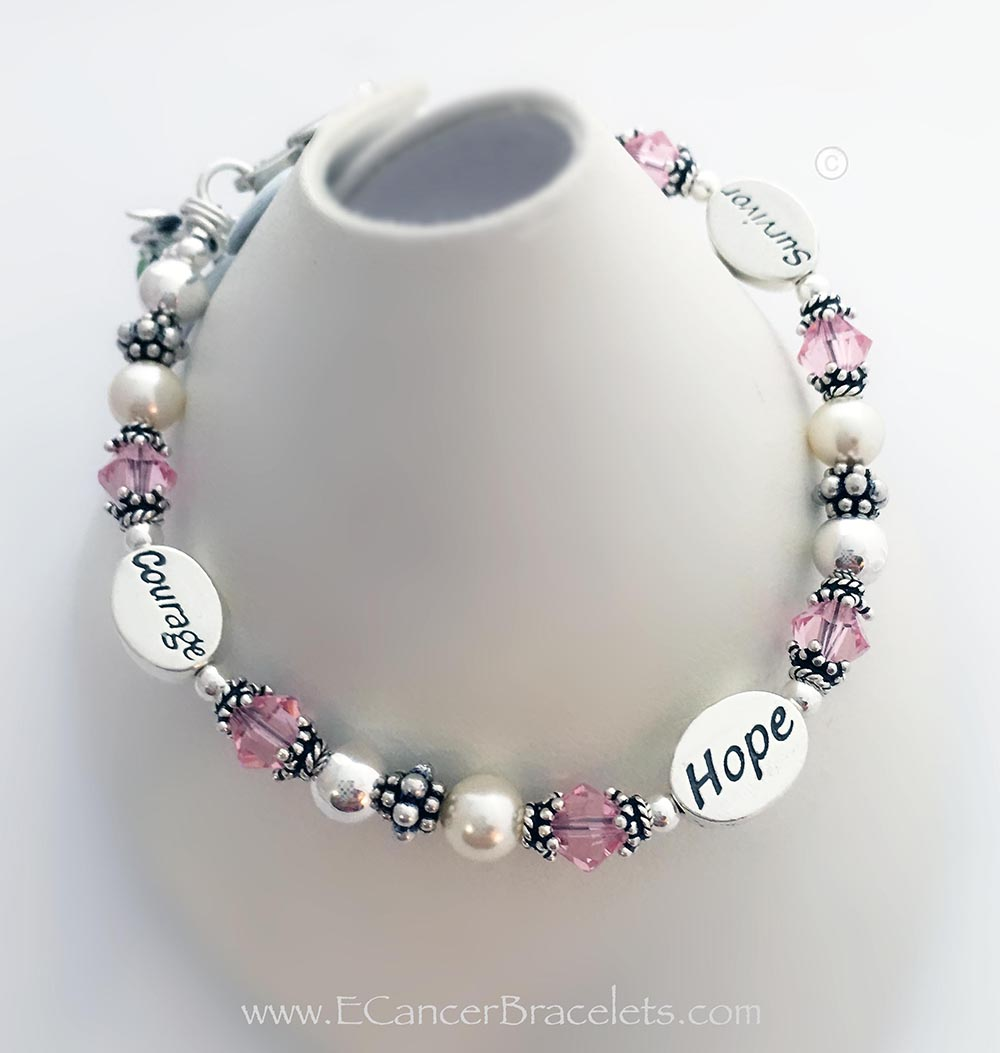 This Pink Ribbon Bracelet is shown with 3 message beads: Courage, Hope and Survivor. The bracelet comes with a Ribbon Charm.