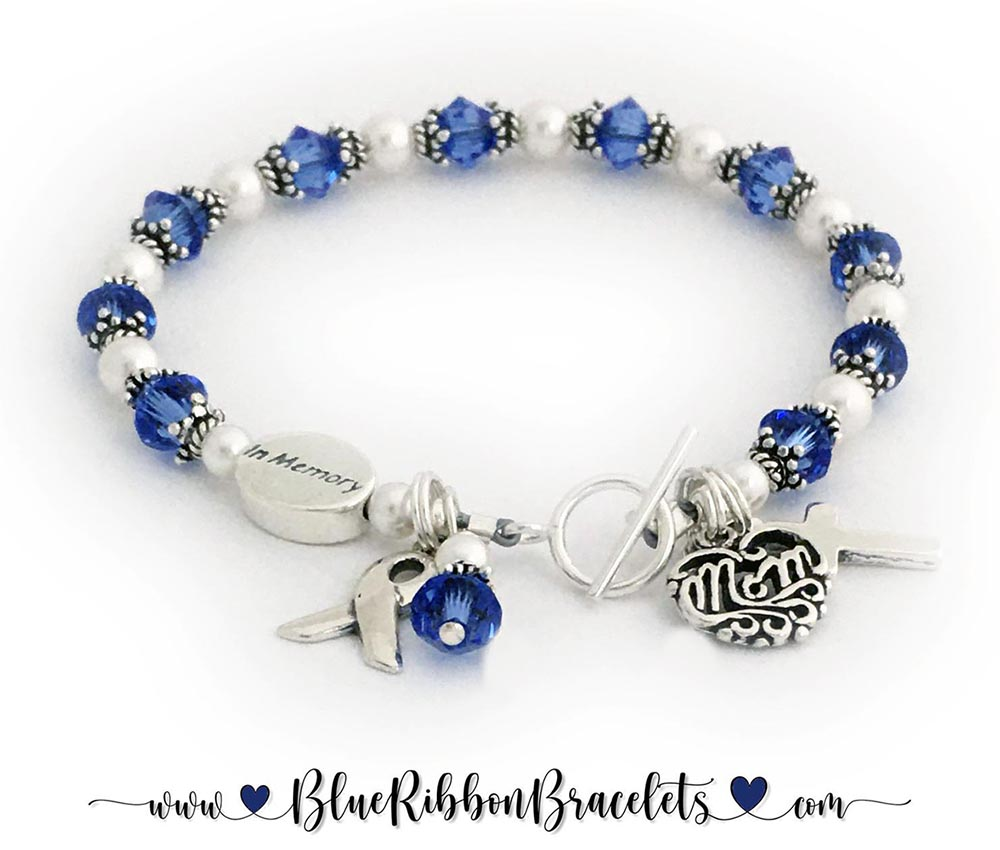 CBB-Ribbon 31  Colon Cancer In Memory Ribbon Bracelet (dark blue/sapphire) Crystals: Bicone/Diamond Message Bead: In Memory Color: Dark Blue/Sapphire Clasp: Small Toggle Charms: (2 charms are included: Ribbon and Crystal Dangle) They added 2 more charms: Filigree MOM Heart Charm and a Simple Cross Charm.