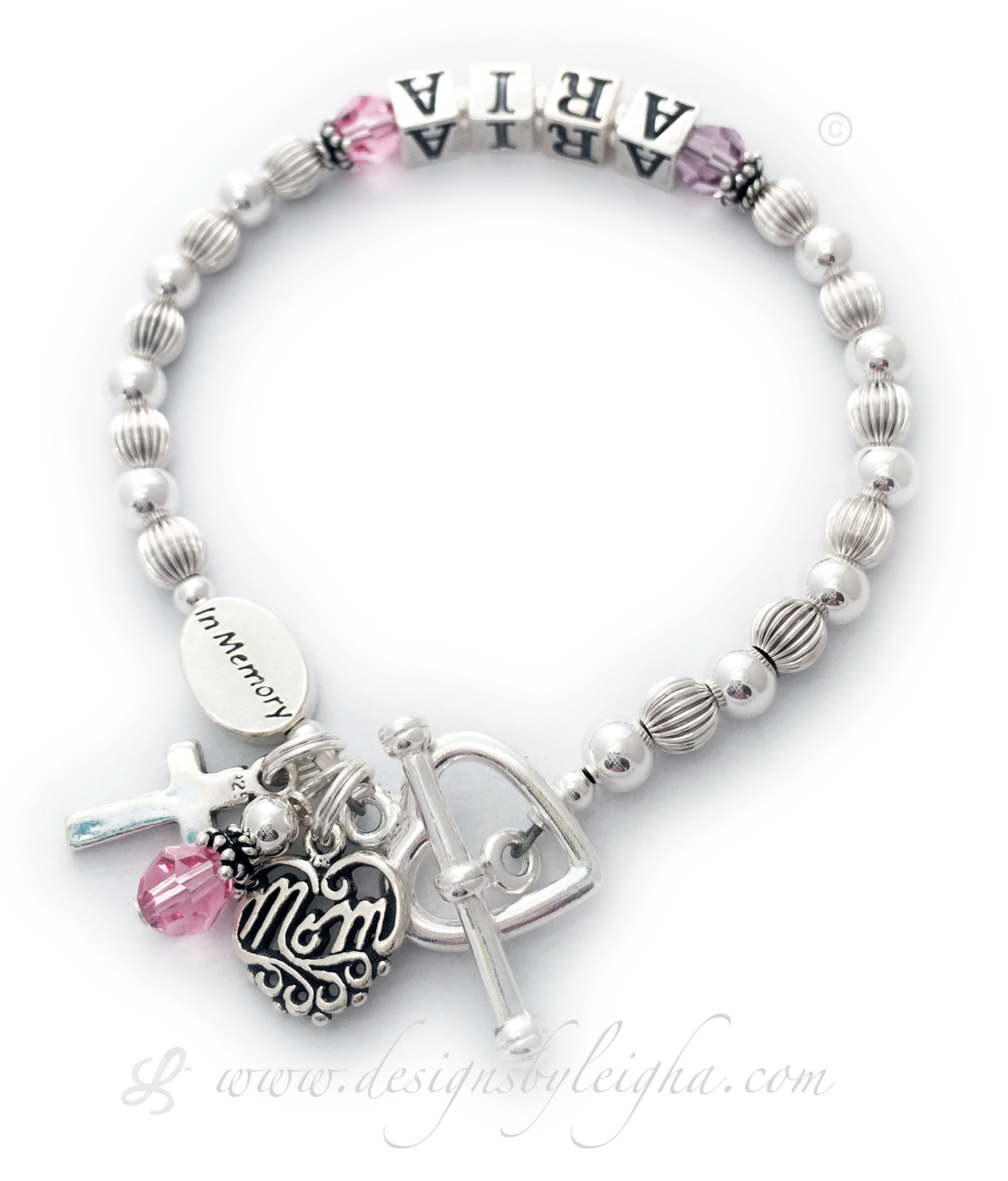 This In Memory Bracelet comes with an IN MEMORY bead and a crystal dangle. They upgraded the free toggle clasp to a Heart Toggle Clasp and added 2 additional charms: Simple Cross Charm and a Filigree Mom Charm. You choose the name and colors of crystals. They chose ARIA and pink for breast cancer.